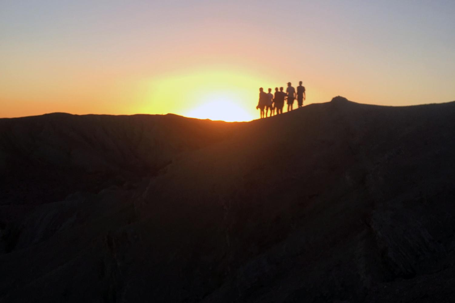 Freshmen boys stand over the desert hills in Barstow during sunset. Photo courtesy of Arshia Sazi ('22).
