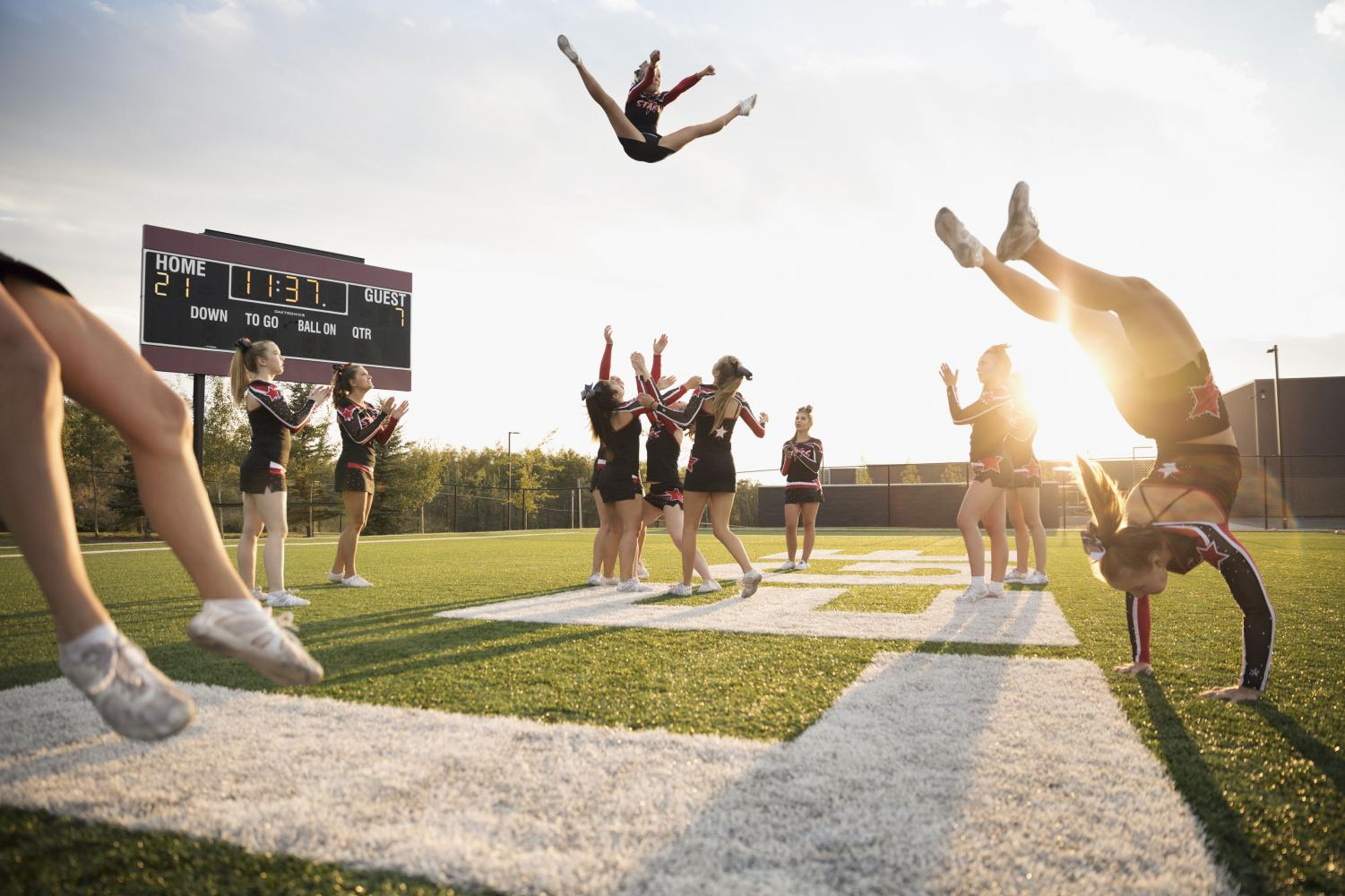 A cheer team jumps, tumbles, and stunts at a game. Graphic courtesy of ThoughtCo.