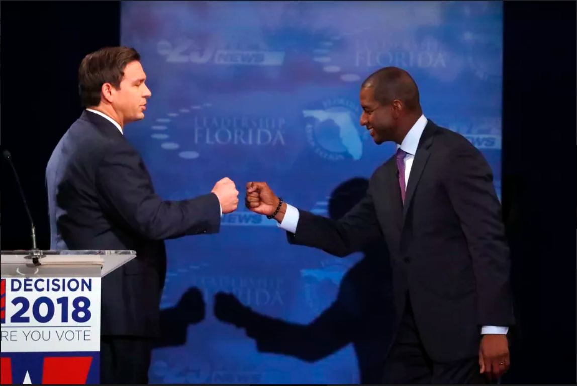 A fist bump between Ron Desantis and Andrew Gillum after a televised debate. Image courtesy of Vox.