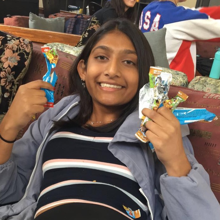 Manek Khedia ('21) holds up a handful of granola bar wrappers.