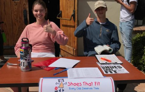 Bridgid Corbin ('19), VWS Head of DSPs, and DSP Liam Gerken ('20) remind students to donate to Shoes That Fit outside of the Hooper Center.