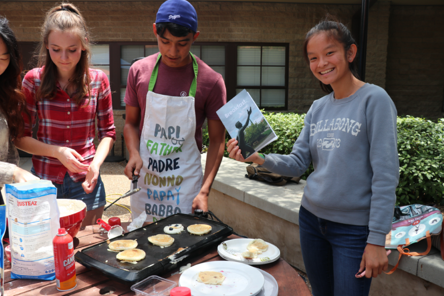 Patrick Dóñez ('21) and Amelie Cook ('20) serve pancakes while Carly Granda ('21) enjoys her copy of Breakfast.