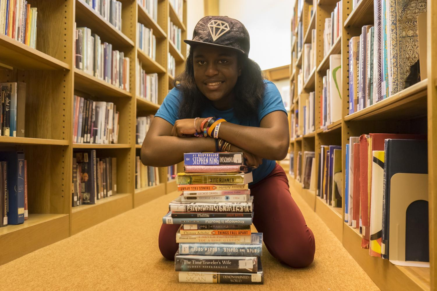 Janina Akporavbare ('22) poses with the 19 books she read for the library's reading challenge.