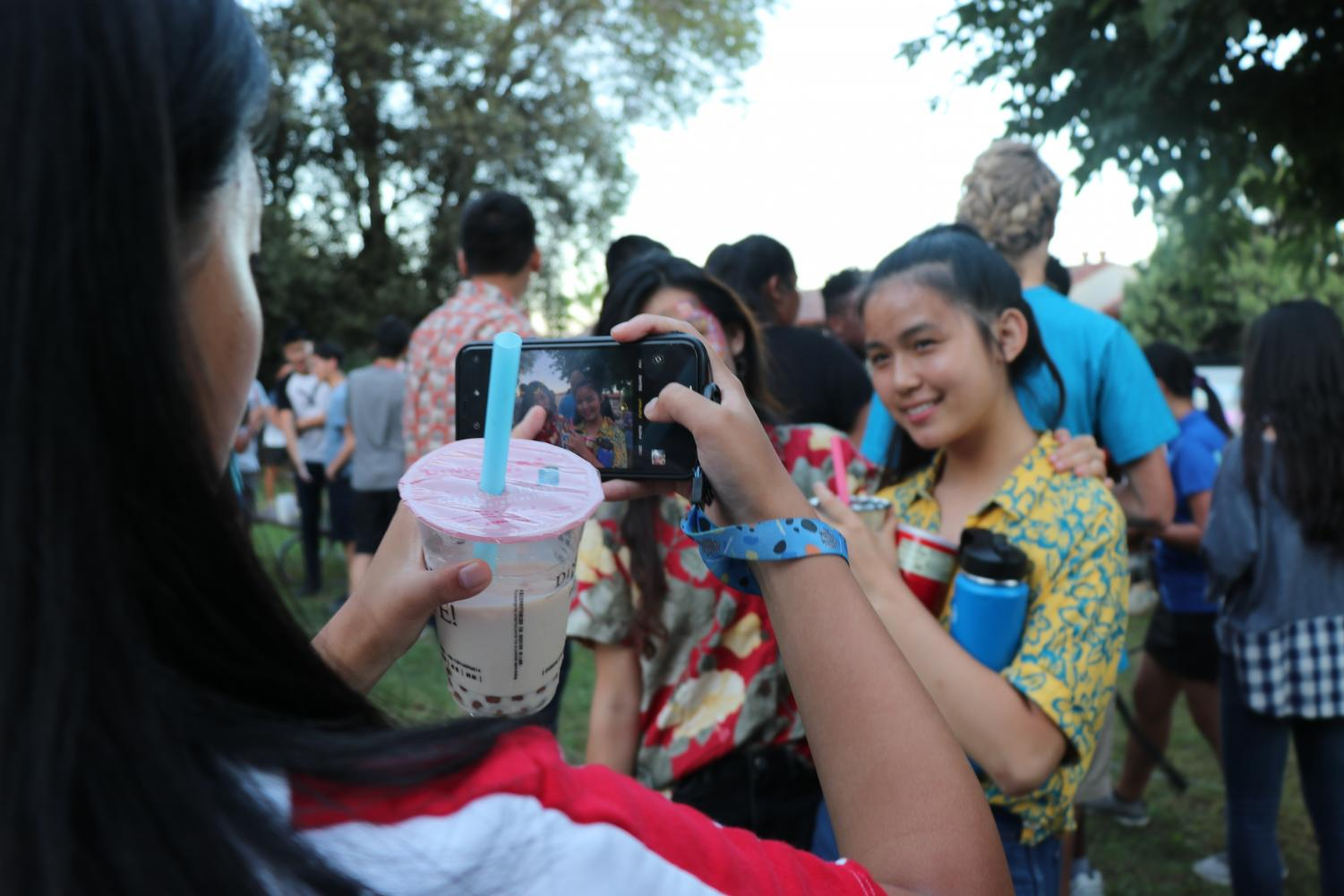 VWS students smile with their intricate face paint designs on display for their friend, who has an iPhone snapping a photo in one hand and a cup of Ding Tea boba in the other.