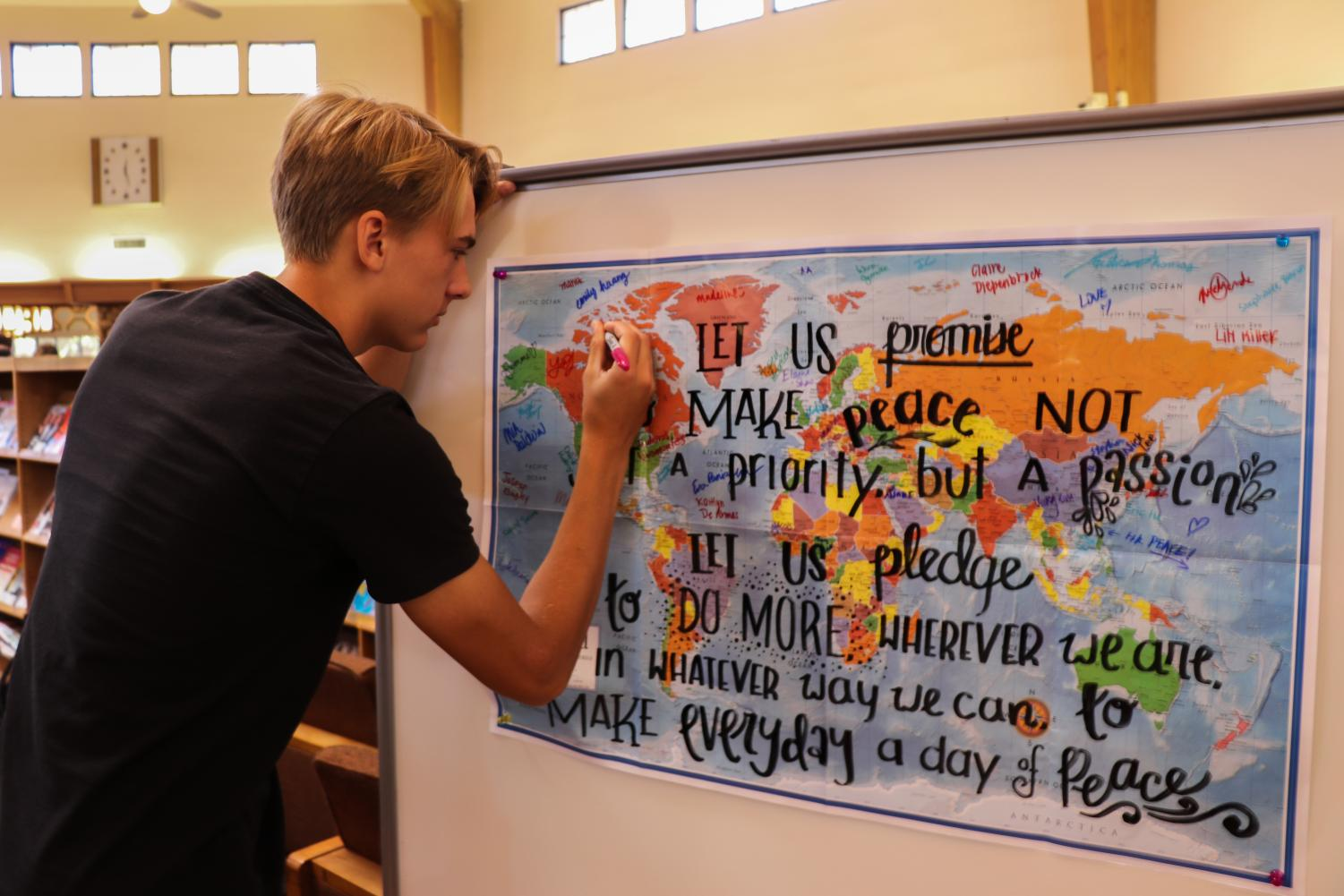 Ethan Caldecott ('21) signs his name on the world map, taking the peace pledge.