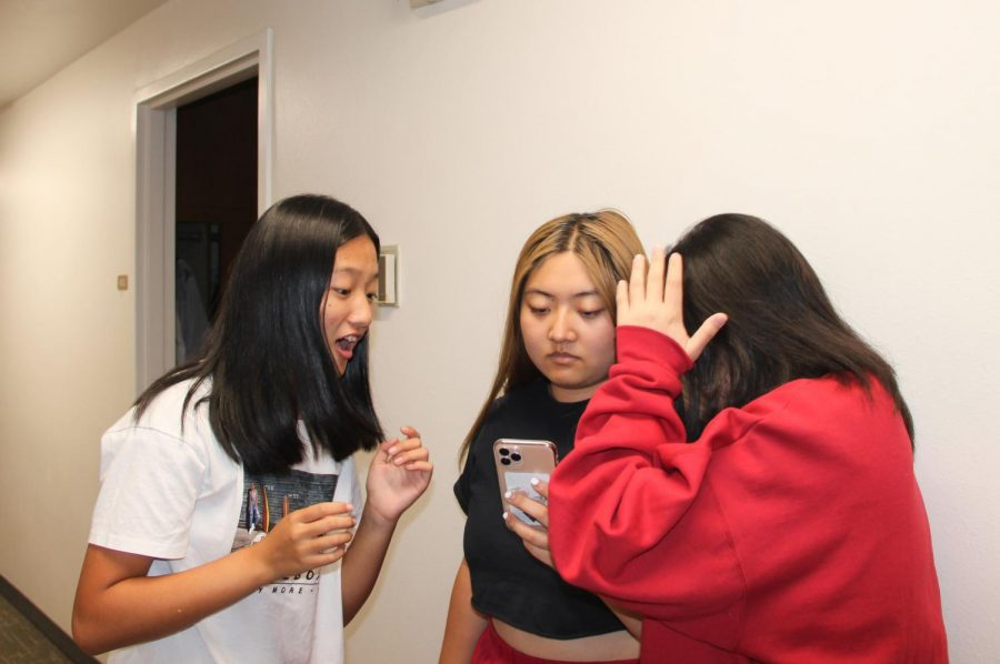 Jessica Cao ('23) and Catherine Li ('22) look at Angie Chen ('20)'s newly acquired iPhone in awe.