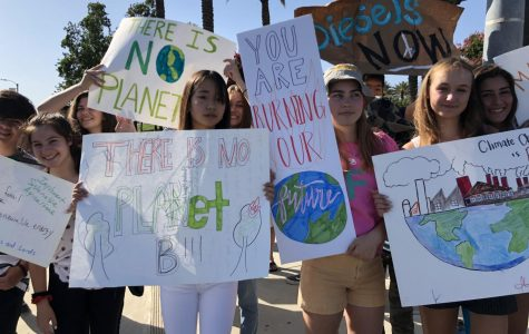 Students hold posters they made from recycled materials during the Rancho Cucamonga climate strike.