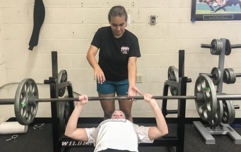 Julia Patronite ('21) spots Livia Hughson ('21) in bench press as she tries to become a stronger swimmer.