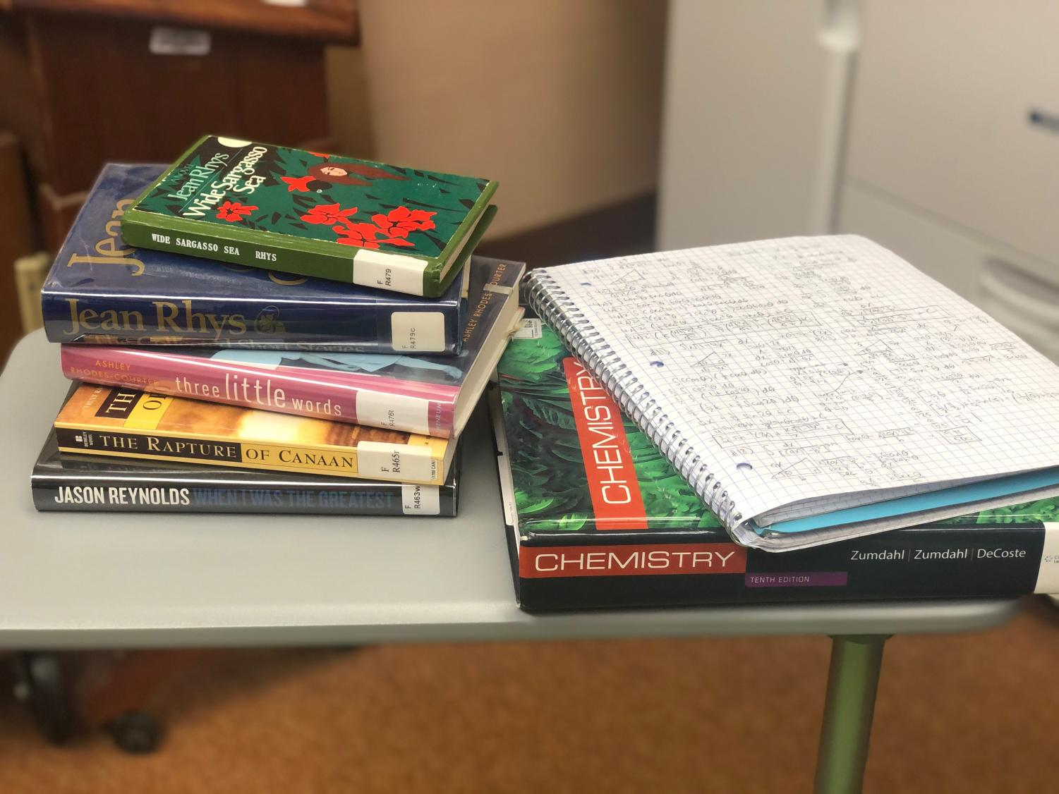 A Webbie's belongings are piled on a desk: chemistry textbook, math notebook, and five library books.