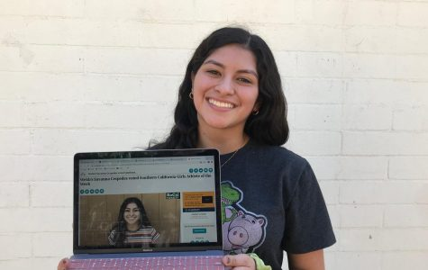 Savanna Cespedes ('22) holds open the website announcing her victory.