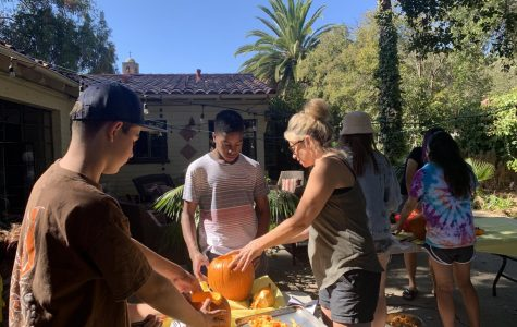 Romana Quick, ISP coordinator, helps Ochuru Ochuru ('23) and Aidan Helgeson ('23) with their pumpkins.