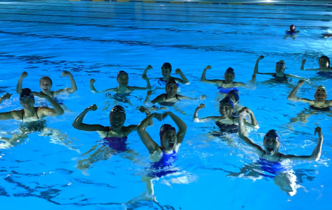 The Vivian Webb water polo team flexes in the pool after completing the Hour of Power.