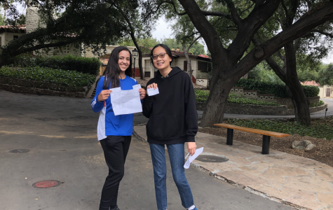 Katie Arzate ('23) and Yvette Shu ('23) smile at Crossroads with commodities that they are hoping to use to earn more money in the game.