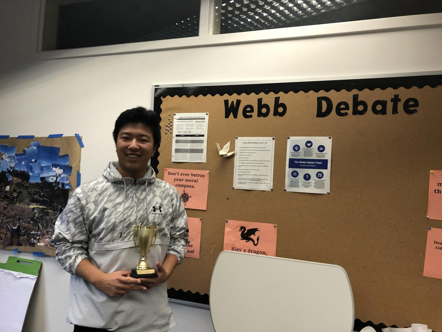 Hanson Hu ('23) holds the second place trophy.