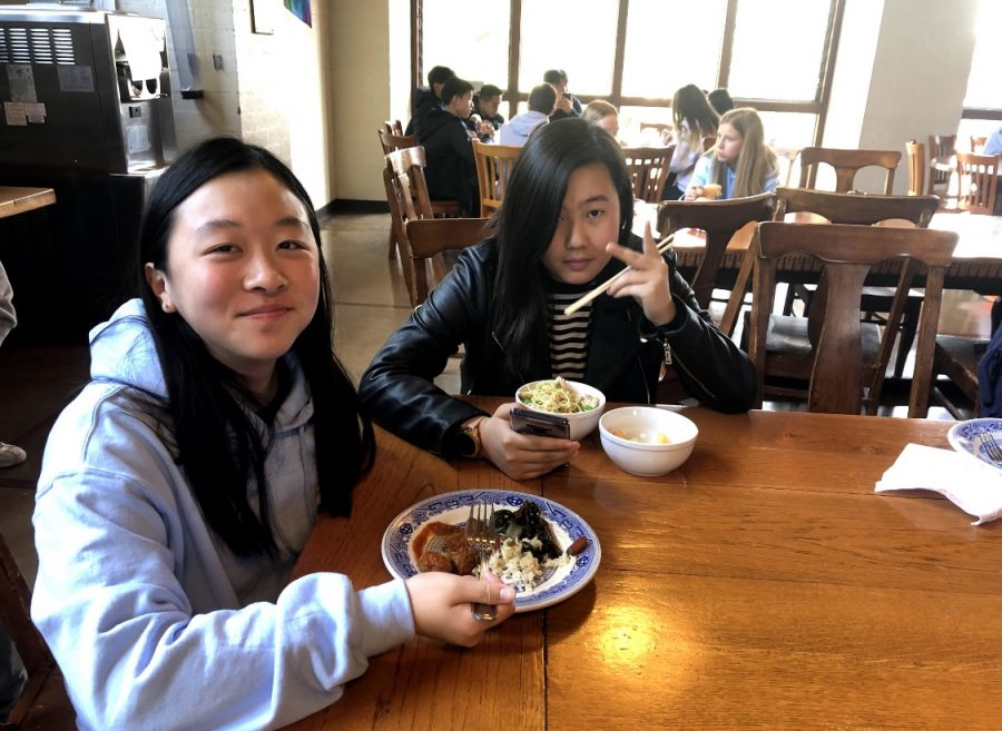 Yvonne Kang ('22) and Leslie Huh ('22) eat lunch in the dining hall.