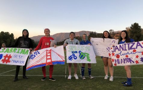 Seniors on the team, including manager Sabrina Chavez ('20), Bridgette Lee ('20), Tina Kabbouche ('20), Molly Mitchell ('20), Shelby Mocrkicky ('20), and Janitza Luna ('20), pose with senior game posters after the game. Graphic courtesy of Janitza Luna.