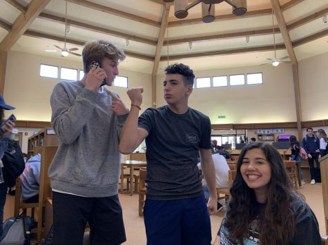 Claire Diepenbrock ('21), Max Fargo ('21), and Johnathon Maschler ('21) listen and dance to music in the library.