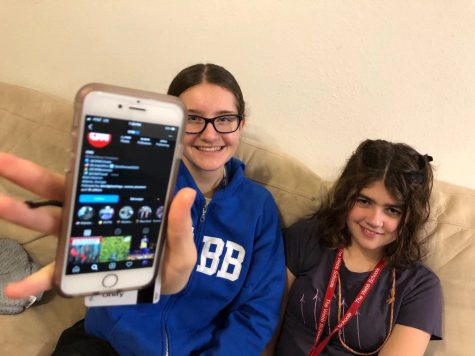 Molly Ratinoff ('23) and McKenna Boyle ('23) hold the phone that shows CNN's Instagram page.