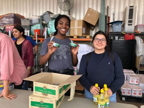 Nnenna Ochuru ('21) and Rebeca Castro ('20) hold food supplies and get ready to serve.