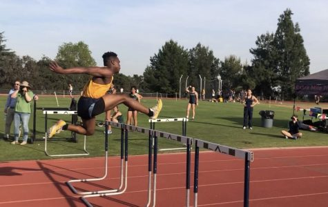 Christopher Haliburton ('20) jumps over the last hurdle to finish the race.
