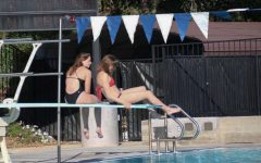 Livia Hughson ('21) and Kennedy Becher ('21) spend time on the diving board before swim practice.