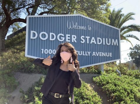 "Skyler Rivera ('18) stands in front of Dodger Stadium because she cannot be there to watch games. ""The Dodger fan base is legendary, they ride or die and so for this team to win, especially in a time like this where the mood of the country is down and out, it's a real mood booster,"" Skyler said."