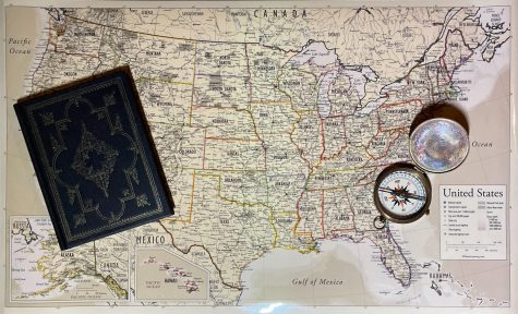 The map of the USA, propped with a worn compass and a leather book.