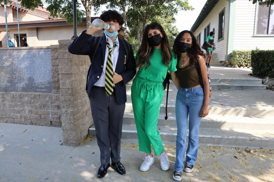 Jonathon Rosales ('24), Nicole Rabadi ('24), and Xajani Badkar ('24) stand in front of the Old School House dressed as Boss Baby and two Shreks.